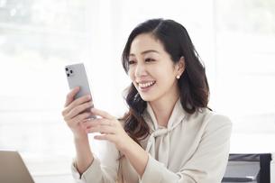 スマートフォンを持ち会話する女性とノートパソコンの写真素材 [FYI04527188]