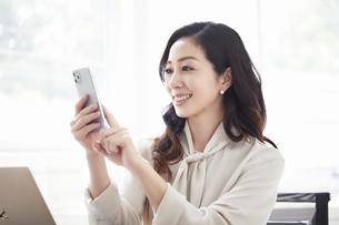 スマートフォンを持ち会話する女性とノートパソコンの写真素材 [FYI04527189]