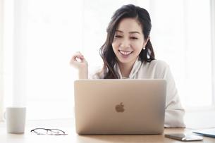 仕事をする女性とノートパソコンの写真素材 [FYI04527202]