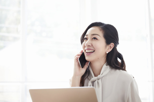 スマートフォンを持ちながら仕事をする女性の写真素材 [FYI04527214]
