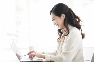 ノートパソコンを使いながら仕事をする女性の写真素材 [FYI04527216]