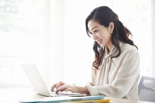 ノートパソコンを使いながら仕事をする女性の写真素材 [FYI04527217]