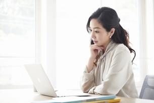 ノートパソコンを使いながら仕事をする女性の写真素材 [FYI04527218]