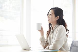 ノートパソコンを使いながら仕事をする女性の写真素材 [FYI04527219]