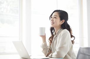 ノートパソコンを使いながら仕事をする女性の写真素材 [FYI04527220]