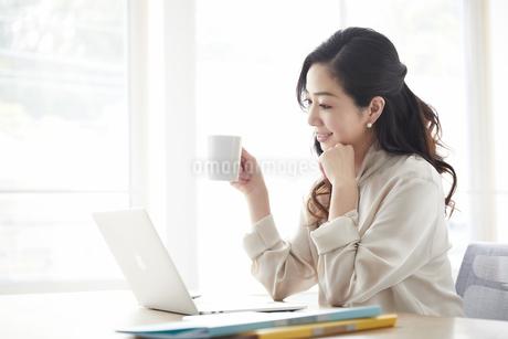 ノートパソコンを使いながら仕事をする女性の写真素材 [FYI04527221]