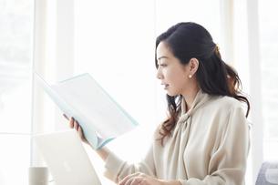 ノートパソコンを使いながら仕事をする女性の写真素材 [FYI04527225]