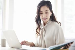 ノートパソコンを使いながら仕事をする女性の写真素材 [FYI04527226]