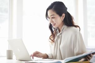 ノートパソコンを使いながら仕事をする女性の写真素材 [FYI04527227]