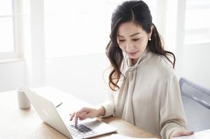 ノートパソコンを使いながら仕事をする女性の写真素材 [FYI04527228]