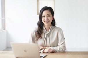 ノートパソコンを使いながら仕事をするカメラ目線の女性の写真素材 [FYI04527236]