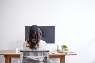 パソコンを使いながら仕事をする女性の後ろ姿の写真素材 [FYI04527239]