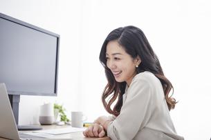 ノートパソコンを使いながら仕事をする女性の写真素材 [FYI04527247]