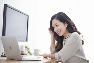ノートパソコンを使いながら仕事をする女性の写真素材 [FYI04527248]