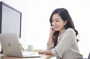 ノートパソコンを使いながら仕事をする女性の写真素材 [FYI04527249]
