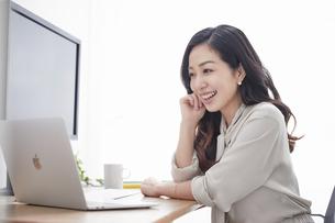 スマートフォンを持ちながら仕事をする女性の写真素材 [FYI04527250]