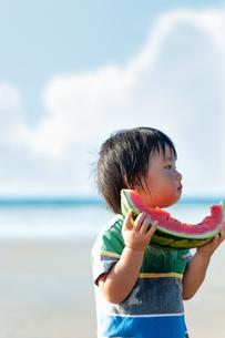 海でスイカを食べる男の子の写真素材 [FYI04528214]
