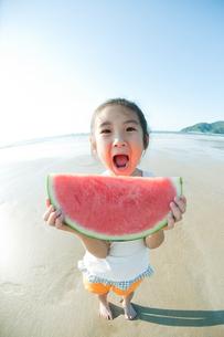 海でスイカを食べる女の子の写真素材 [FYI04528215]