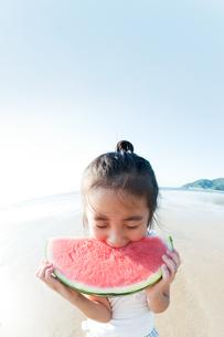 海でスイカを食べる女の子の写真素材 [FYI04528216]