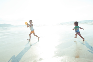 浜辺で走る姉弟の写真素材 [FYI04528219]