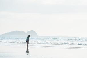波打ち際でたたずむ男の子の写真素材 [FYI04528223]