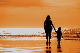 夕暮れの波打ち際を歩く親子のシルエットの写真素材 [FYI04528229]
