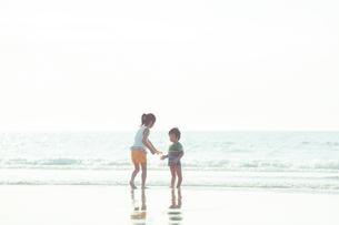 波打ち際で遊ぶ姉弟の写真素材 [FYI04528230]