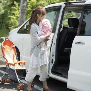 娘を車に乗せる母親の写真素材 [FYI04528918]