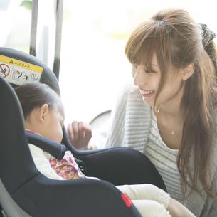 チャイルドシートの娘を見守る母親の写真素材 [FYI04528919]