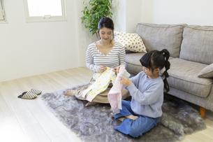 ベビーウェアを準備する母娘の写真素材 [FYI04529984]
