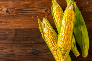 Corn cobs on wood background.の写真素材 [FYI04530577]