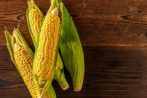 Corn cobs on wood background.の写真素材 [FYI04530578]