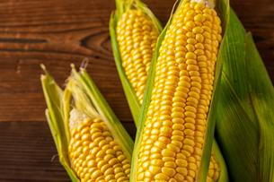 Corn cobs on wood background.の写真素材 [FYI04530581]