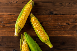 Corn cobs on wood background.の写真素材 [FYI04530584]