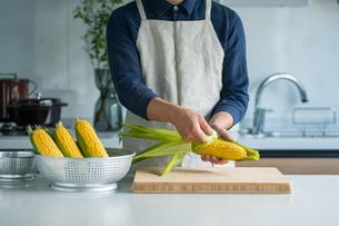 Man peeling corn husk at kitchen.の写真素材 [FYI04530594]