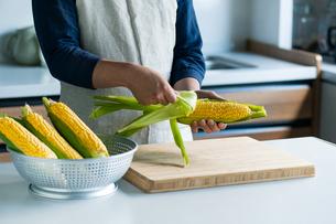 Man peeling corn husk at kitchen.の写真素材 [FYI04530598]