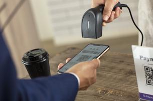 キャッシュレス決済のスマートフォンとバーコードリーダーの写真素材 [FYI04531212]