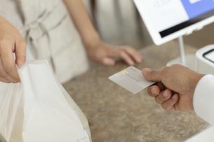 クレジットカードを差し出す客の手元の写真素材 [FYI04531222]