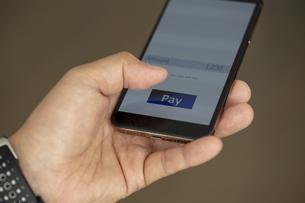 スマートフォンでキャッシュレス決済をする男性の手元の写真素材 [FYI04531236]