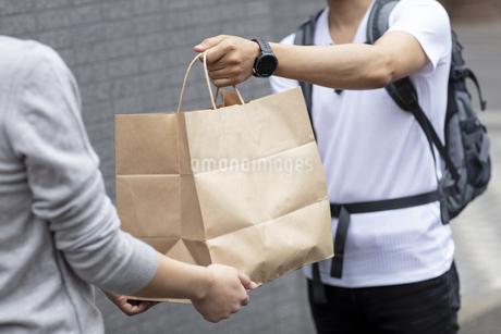 品物を手渡すデリバリースタッフと客の写真素材 [FYI04531239]