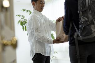 品物を手渡すデリバリースタッフと客の写真素材 [FYI04531247]