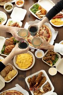 食卓の上のテイクアウトフードと乾杯をする手の写真素材 [FYI04531252]