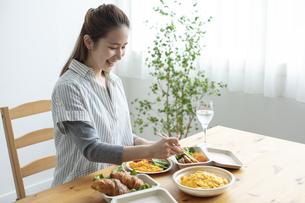 テイクアウトフードで食事をする女性の写真素材 [FYI04531356]