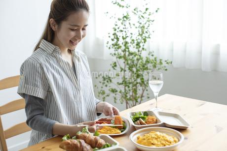 テイクアウトフードで食事をする女性の写真素材 [FYI04531357]