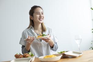 テイクアウトフードで食事をする女性の写真素材 [FYI04531358]