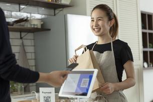 キャッシュレス決済をする客と店員の写真素材 [FYI04531367]