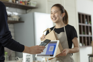 キャッシュレス決済をする客と店員の写真素材 [FYI04531368]