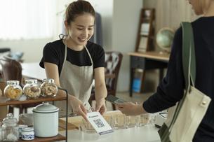 キャッシュレス決済をする客と店員の写真素材 [FYI04531373]