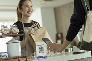 キャッシュレス決済をする客と店員の写真素材 [FYI04531375]