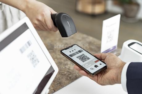 キャッシュレス決済のスマートフォンとバーコードリーダーの写真素材 [FYI04531404]